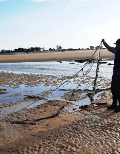 Un des agents de la réserve désensable un filet de pêche illégalement posé dans la réserve